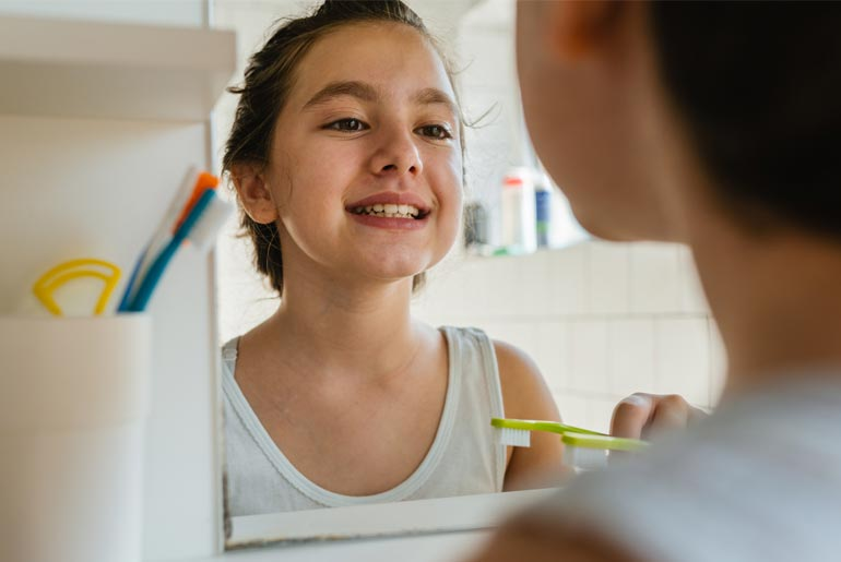 pacifica girl doing dental checkups in mirror